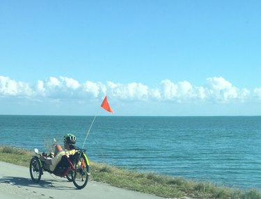 Man Riding Recumbent Bike On Road By Sea Against Blue Sky
