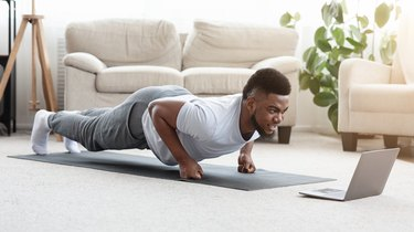 Black Man doing Fist Plank Exercise In Front Of Laptop on gray yoga mat