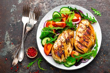 Top view of grilled chicken breast and fresh vegetable salad of tomatoes, cucumbers and arugula leaves