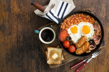 Full English breakfast with sausages, bacon, fried eggs, beans, toast and cup of coffee on wooden table with copy space