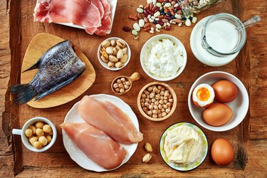High-protein foods like fish, eggs, chicken, beans, milk and nuts on a wooden table