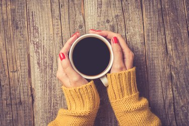 Female hands in warm sweater holding cup of coffee