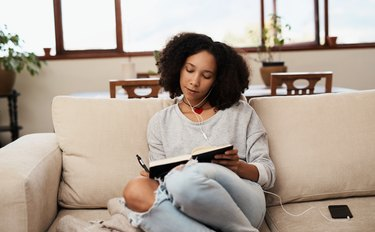Woman on the couch writing in notebook