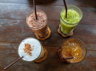 Traditional thai soft drinks on an old rustic wooden table; iced green tea with cream, ice coffee, fruit and herbal drink