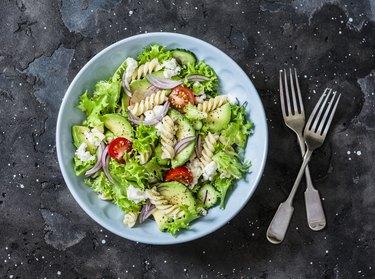 Mediterranean pasta avocado salad on a dark background, top view. Vegetarian diet food concept