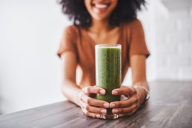 Woman holding green drink.
