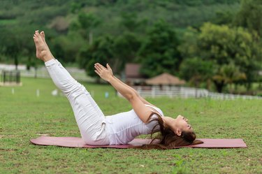 Woman practice yoga Dead Body pose or Uttana Padasana pose