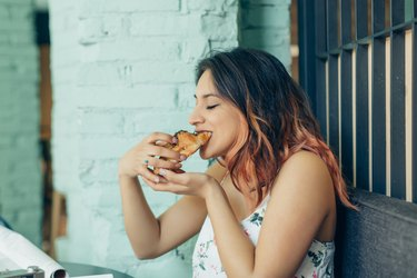 Woman eating croissant in coffee shop