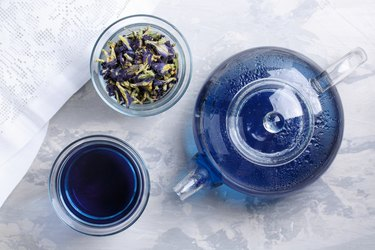 Butterfly pea flower tea is brewed in a glass teapot and served into a transparent cup. Blue herbal tea. Top view.