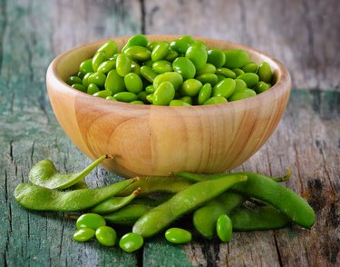 Magnesium- and potassium-rich green soy beans (edamame) in the wood bowl on table