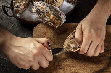 Shucking an oyster, man's hands holding a knife, opening oysters