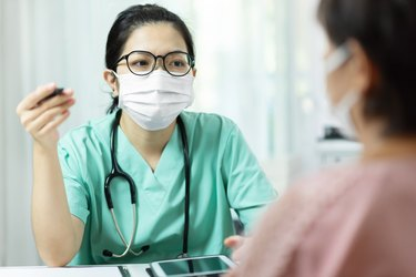Asian female Doctor in green uniform wearing glasses and face mask talking to patient