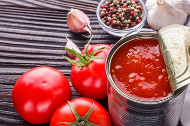 juicy canned tomatoes on wooden rustic background