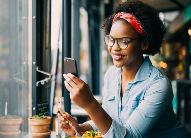A woman wearing glasses and eating a lunch with foods good for eye health