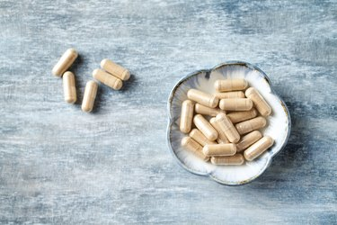 Ashwagandha (Withania somnifera) capsules. Concept for a healthy dietary supplementation. Rustic wooden background. Directly Above. Copy space.