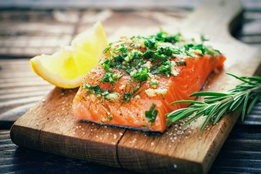 Salmon fillet topped with dill and garlic, served with lemon and rosemary