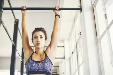 Low angle view of young female trying to do a pull-up