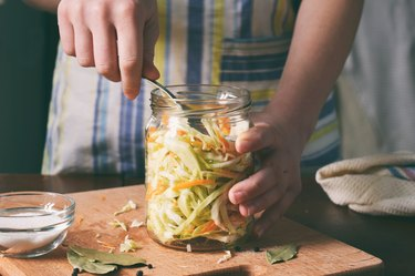 close up of woman's hands adding fermented preserved cabbage to jar with spoon