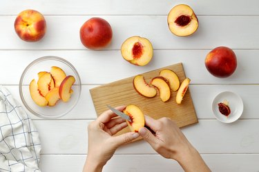 Step by step recipe galette or pie with nectarines. Female hands cut nectarines into slices for cake.
