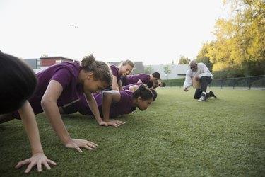 Physical education teacher encouraging students doing push-ups