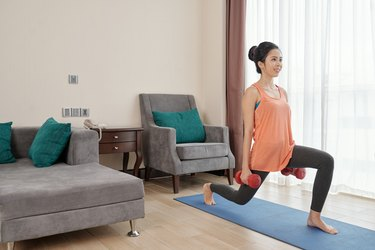 Woman doing weighted lunges with dumbbells on a yoga mat in her living room