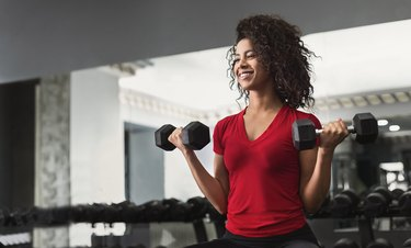African-american fitness woman doing biceps workouts in gym