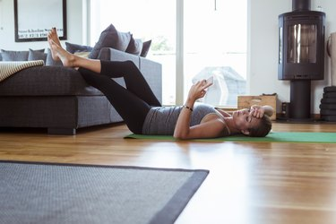 Tired woman using mobile phone while lying on exercise mat in living room