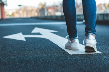 Make decision which way to go. Walking on directional sign on asphalt road.