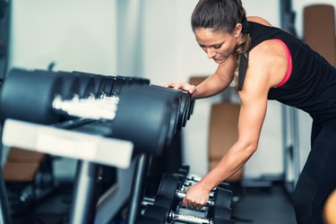 Woman Lifting Dumbbell From Rack In Gym