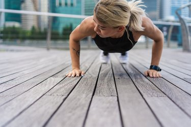 Exercise woman doing push ups in outdoor workout training.
