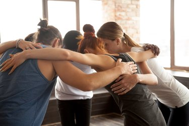 Young people embracing in circle standing together, group unity concept
