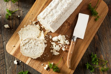 Raw white organic goat cheese on a cutting board.