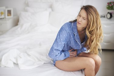 Woman holding her belly in bed