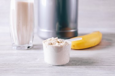Scoop with whey protein powder, banana and glass