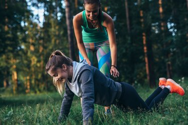 Sporty young female trainer showing a girl how to do knee push-ups while training outdoors in summer