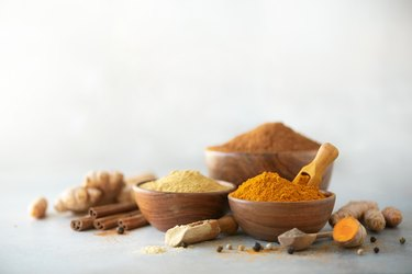 Ingredients for turmeric latte. Ground turmeric, curcuma root, cinnamon, ginger, black pepper on grey background. Spices for ayurvedic treatment. Alternative medicine concept