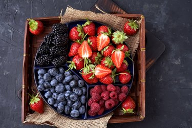 Strawberries, raspberries, blueberries, blackberries on a separate dish close-up on a solid concrete background. Healthy eating Vegan food. View from above