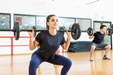 Female Client Exercising With Barbell In Health Club