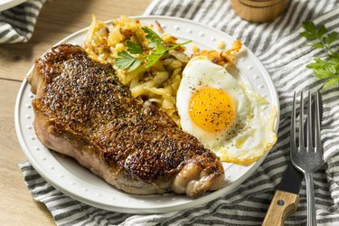 A plate of homemade breakfast, including steak, eggs and potatoes