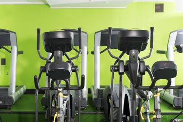 Row of treadmills and ellipticals in a gym for weight loss