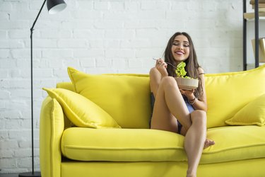 A beautiful young woman is eating a salad in her living room, sitting on a yellow sofa