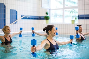 Mature females exercising with foam dumbbells in swimming pool