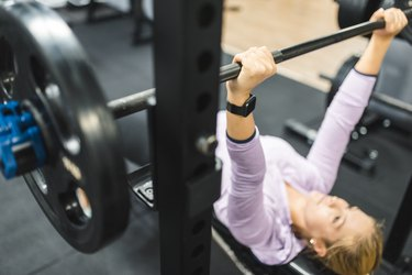 Young woman exercising on the bench press