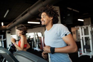 Group of young people running on treadmills as part of their 5-day cardio workout plan