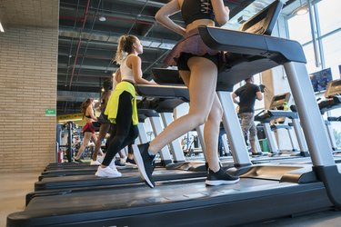 People doing sports on the treadmill inside a gym