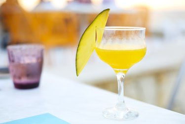 Glass of mango cocktail on bar counter