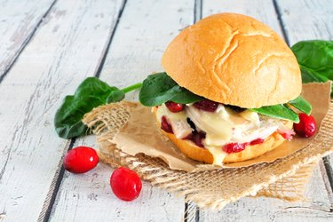 Roasted turkey sandwich with cranberry sauce and cheese, close up on white wood