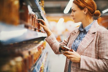 red-haired woman reading ingredients and nutrition label on food products at the grocery store