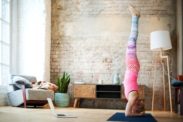 Woman doing Sirsasana (Headstand) during a yoga class at home