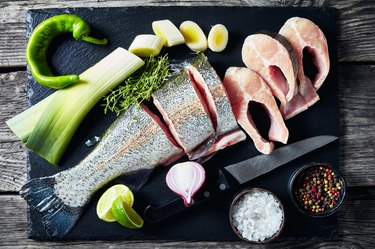 sliced raw trout with lime wedges, leek, thyme, salt and spices on a black stone cutting board